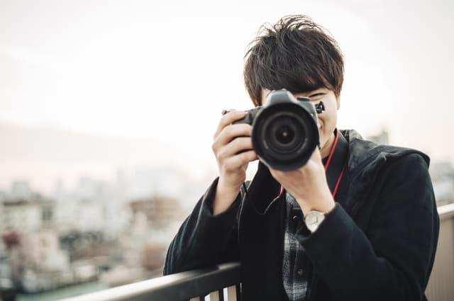 カメラ 持つ 男性